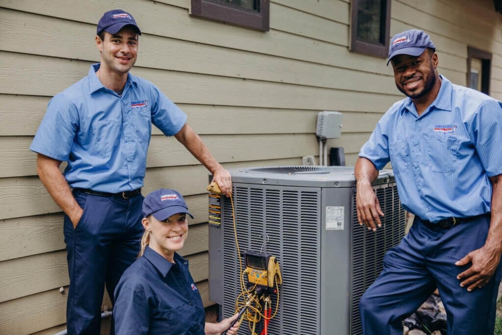 Three HVAC technicians working on an outdoor AC unit