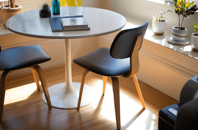 Round table with chairs and small plants around it
