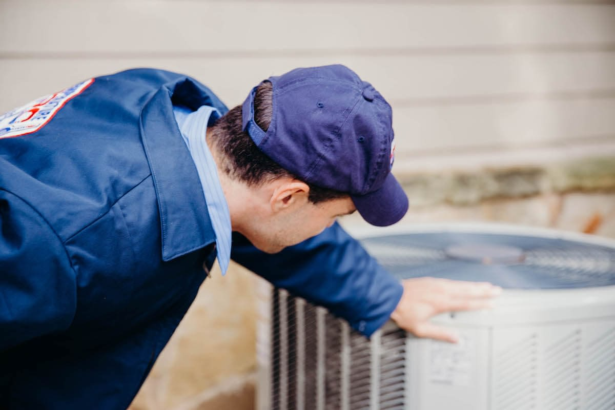 technician inspecting outdoor hvac unit