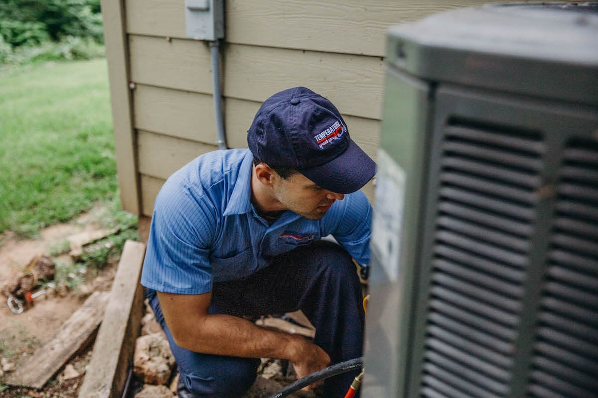 HVAC technician working on an outdoor ac unit