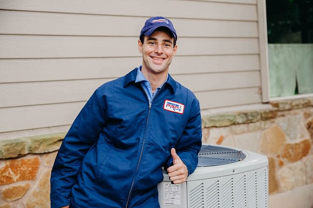 Happy HVAC handyman working outdoors